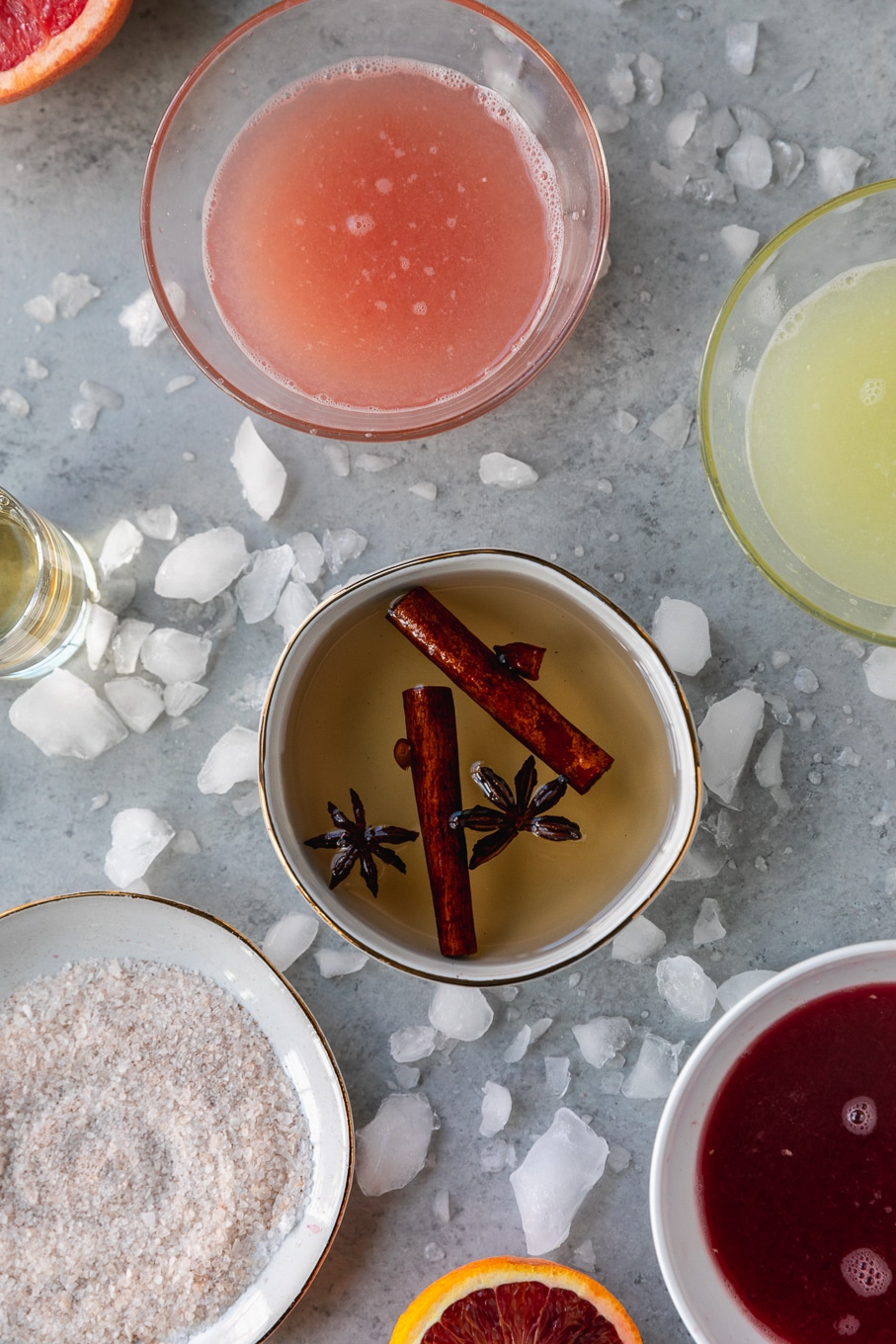 Overhead shot of a bowl of simple syrup with star anise and cinnamon sticks floating in it, surrounded by bowls of lime juice, grapefruit juice, and blood orange juice, with crushed ice scattered around