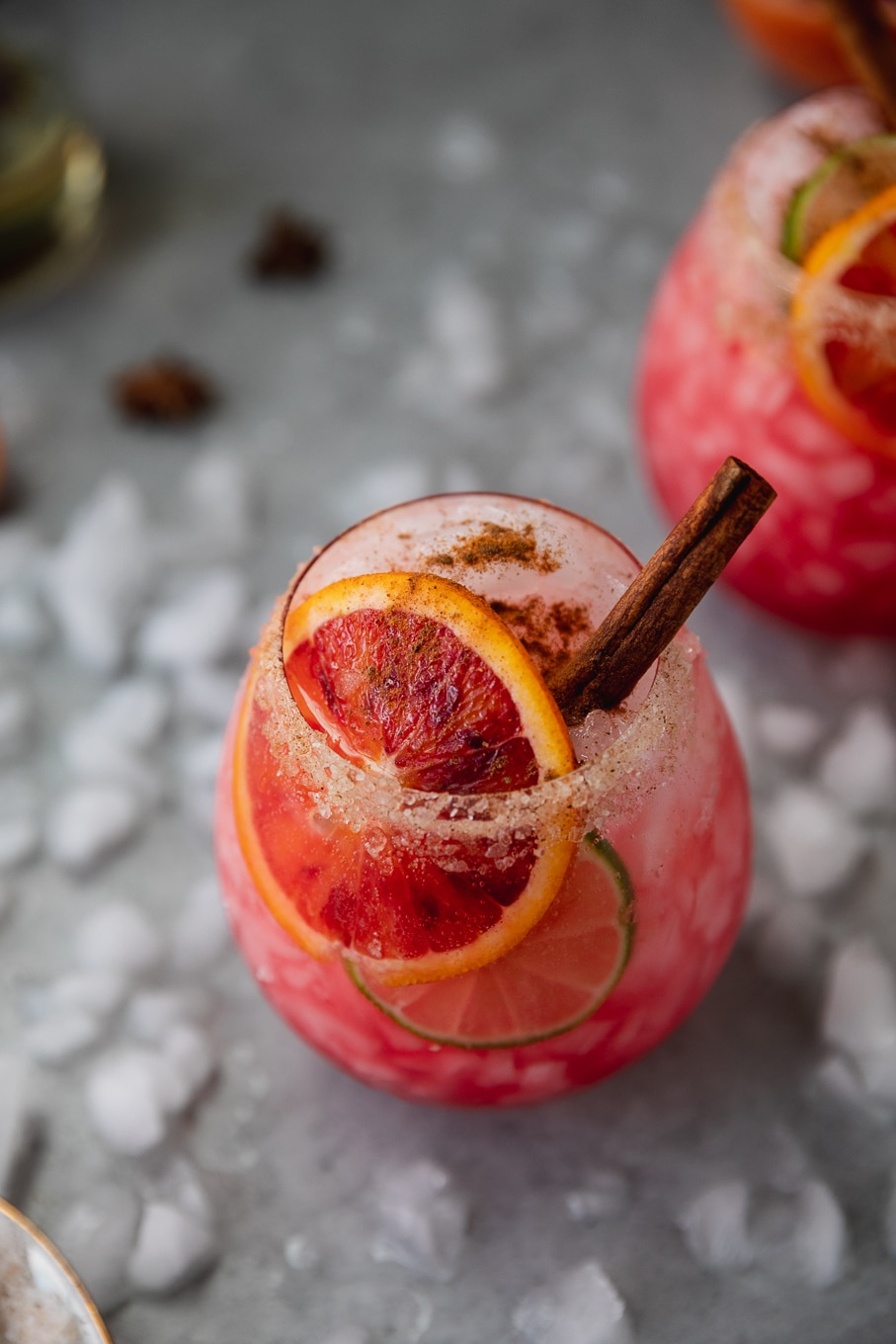 Close up shot of a pink blood orange cocktail garnished with a slice of blood orange, lime, and a cinnamon stick