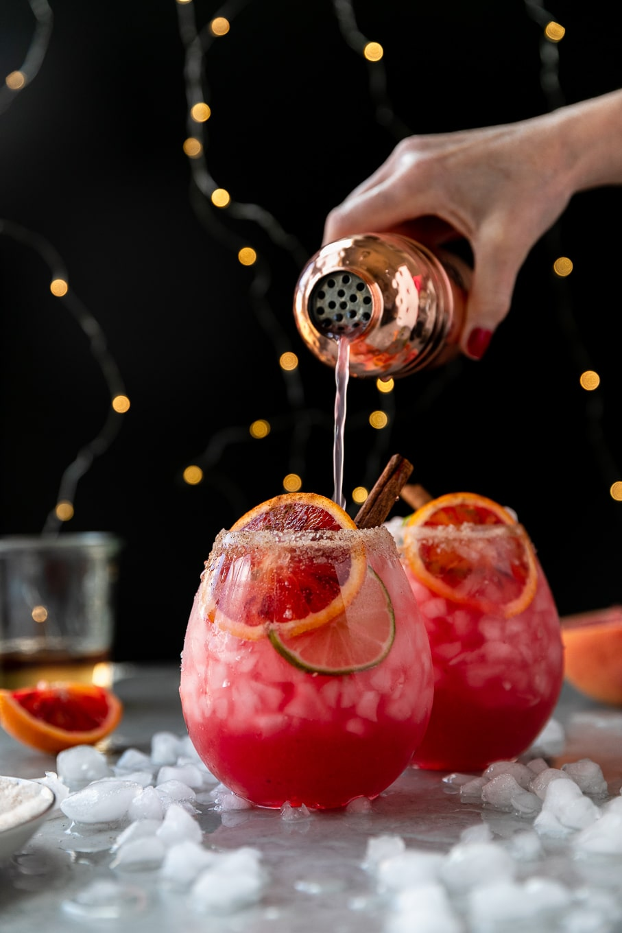 Forward facing shot of a pink blood orange cocktail and a hand pouring the drink into it from a copper cocktail shaker