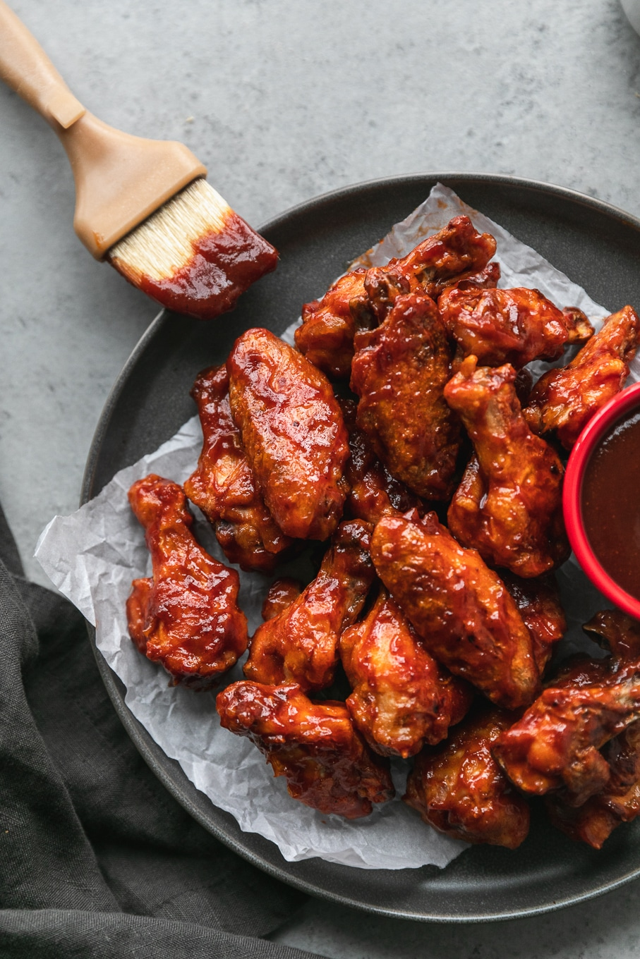 Overhead shot of a plate of BBQ wings with a pastry brush resting on the plate