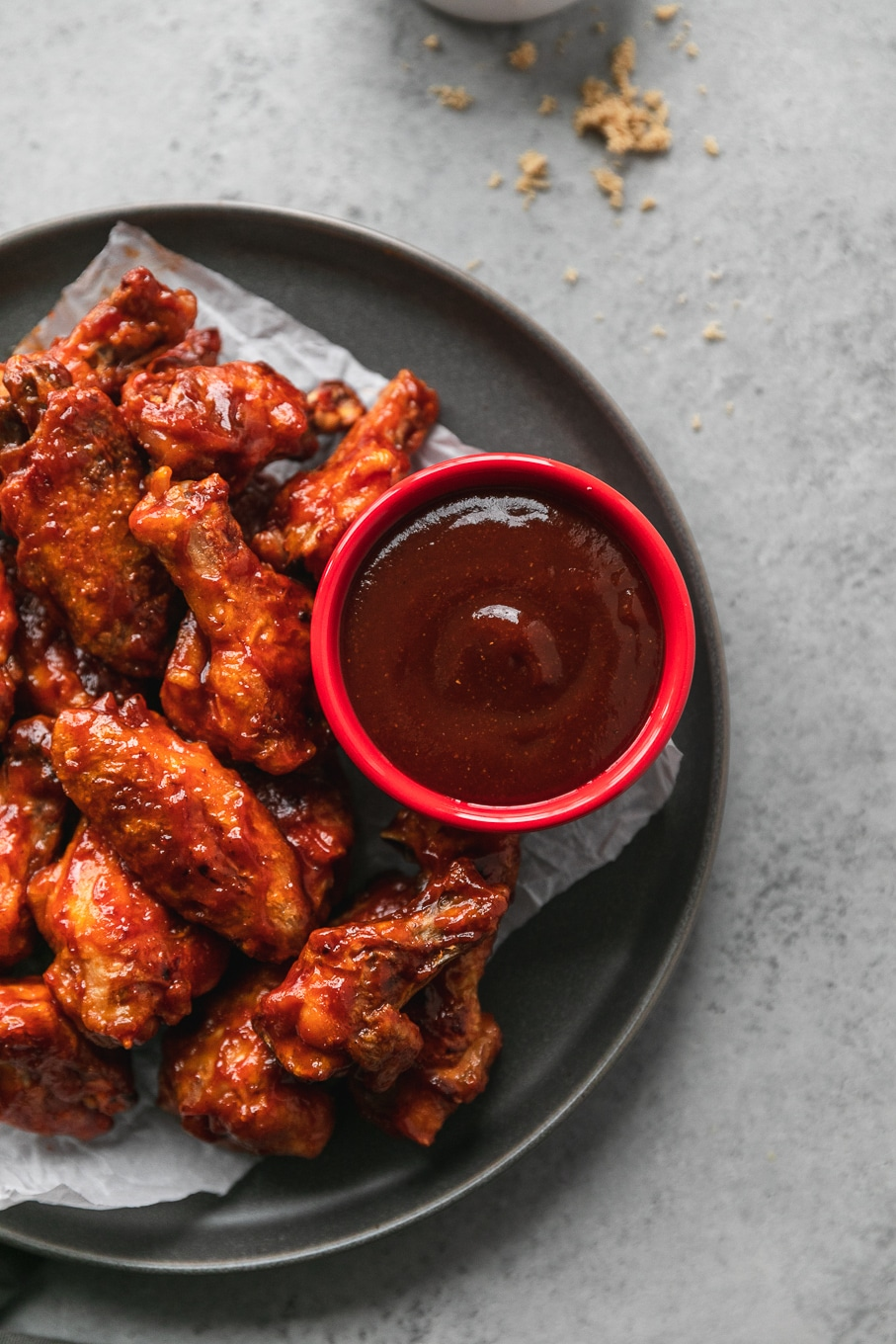 Overhead close up shot of a red ramekin filled with BBQ sauce on a grey plate with wings
