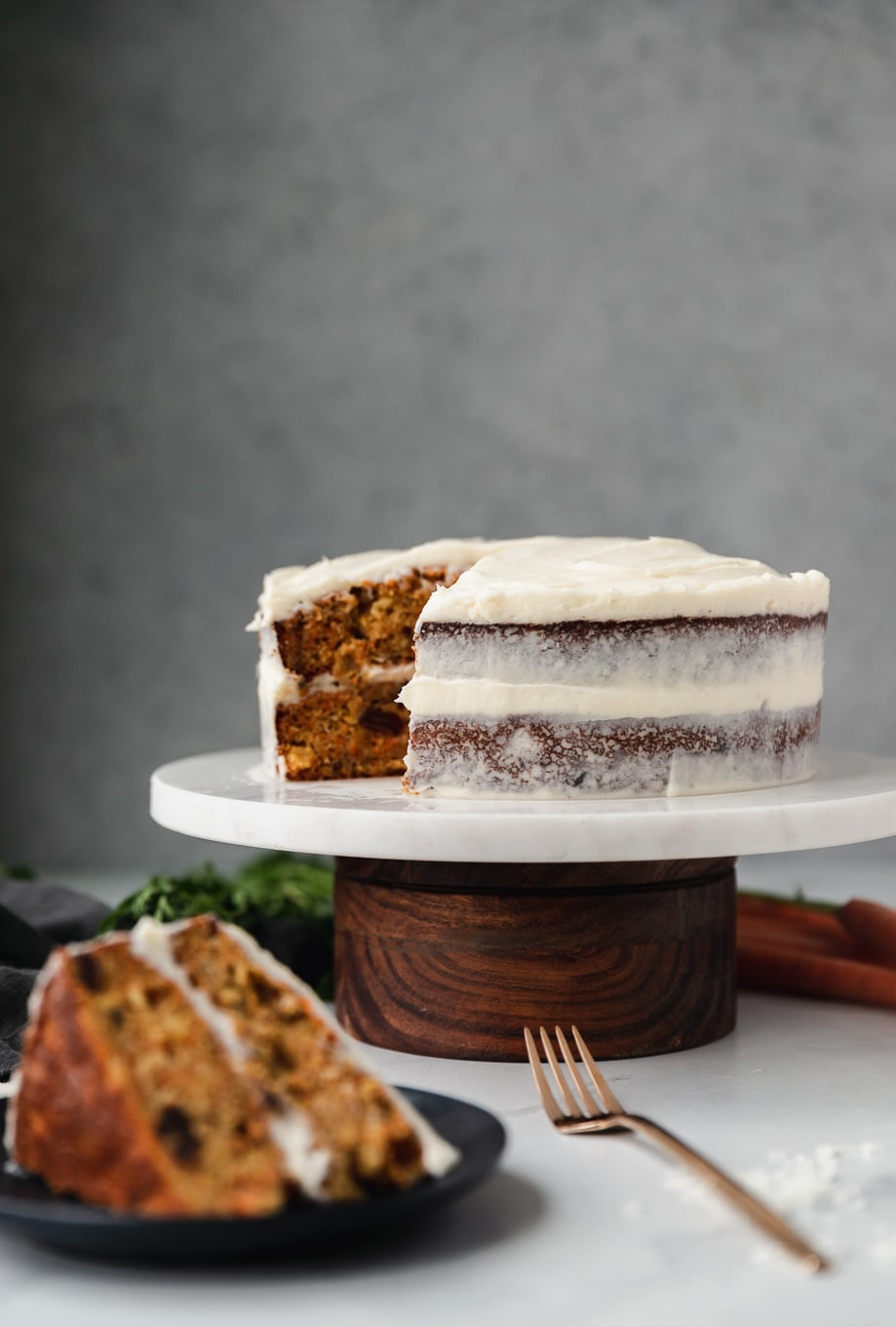 Forward facing shot of a carrot cake on a marble and wooden cake stand with a slice of cake on a black plate in front of it