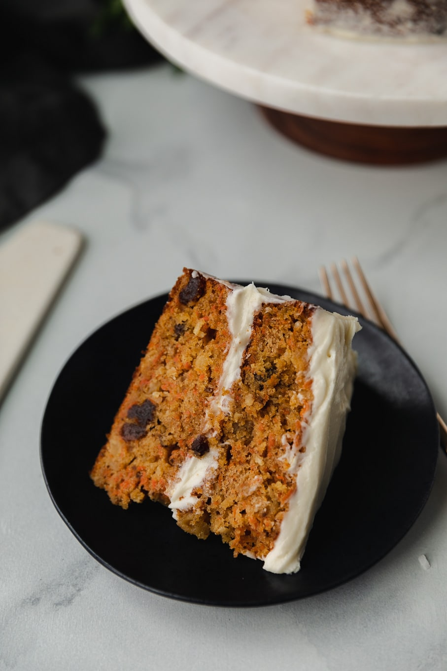Close up shot of a slice of carrot cake on a black plate