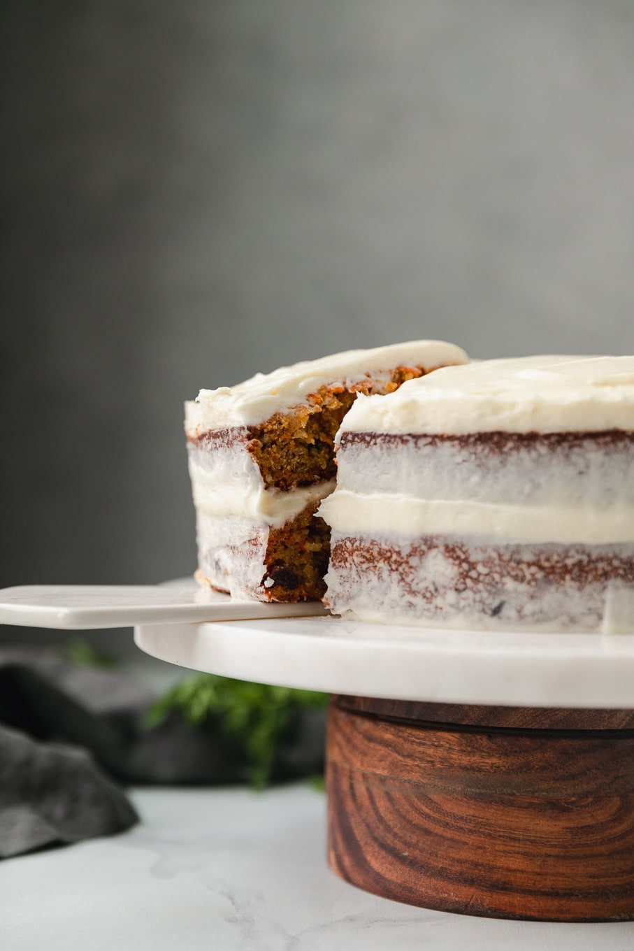Forward facing shot of a carrot cake on a marble and wooden cake stand with a slice being taken out of the cake