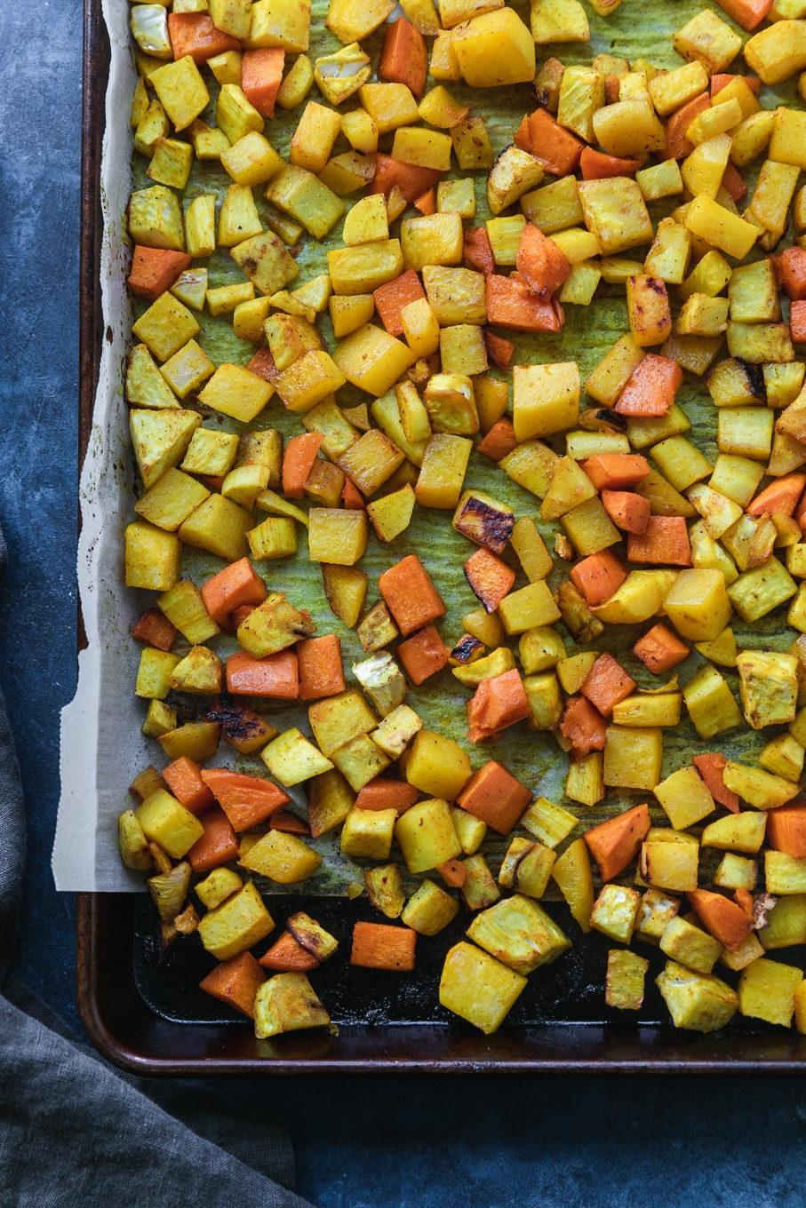 Overhead shot of a sheet pan filled with roasted yellow and orange root vegetables