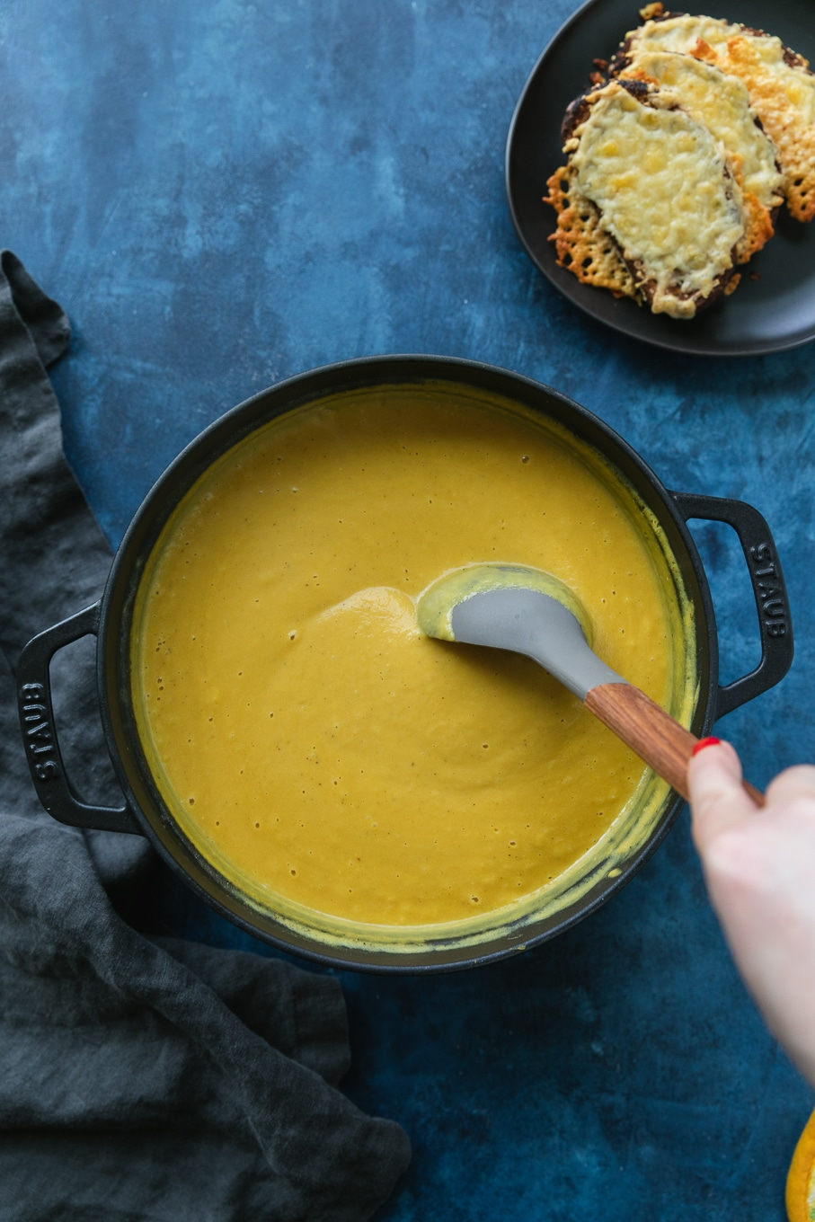 Overhead shot of a black cast iron pot filled with orange soup and a hand stirring it with a grey and wooden spoon