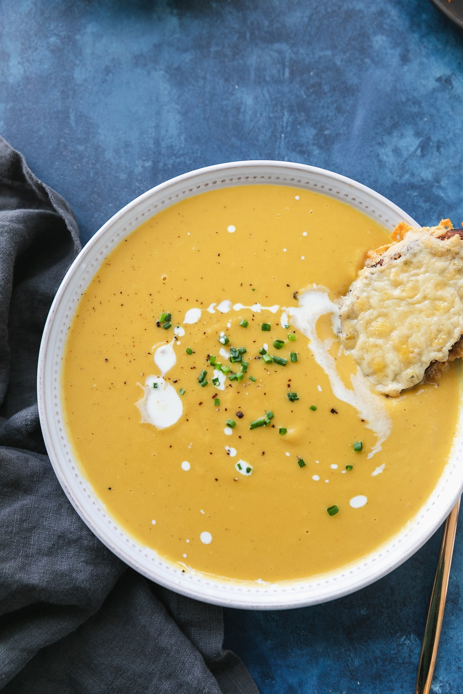 Overhead shot of a bowl of orange soup drizzled with cream and chives, with a cheesy toast resting in the soup