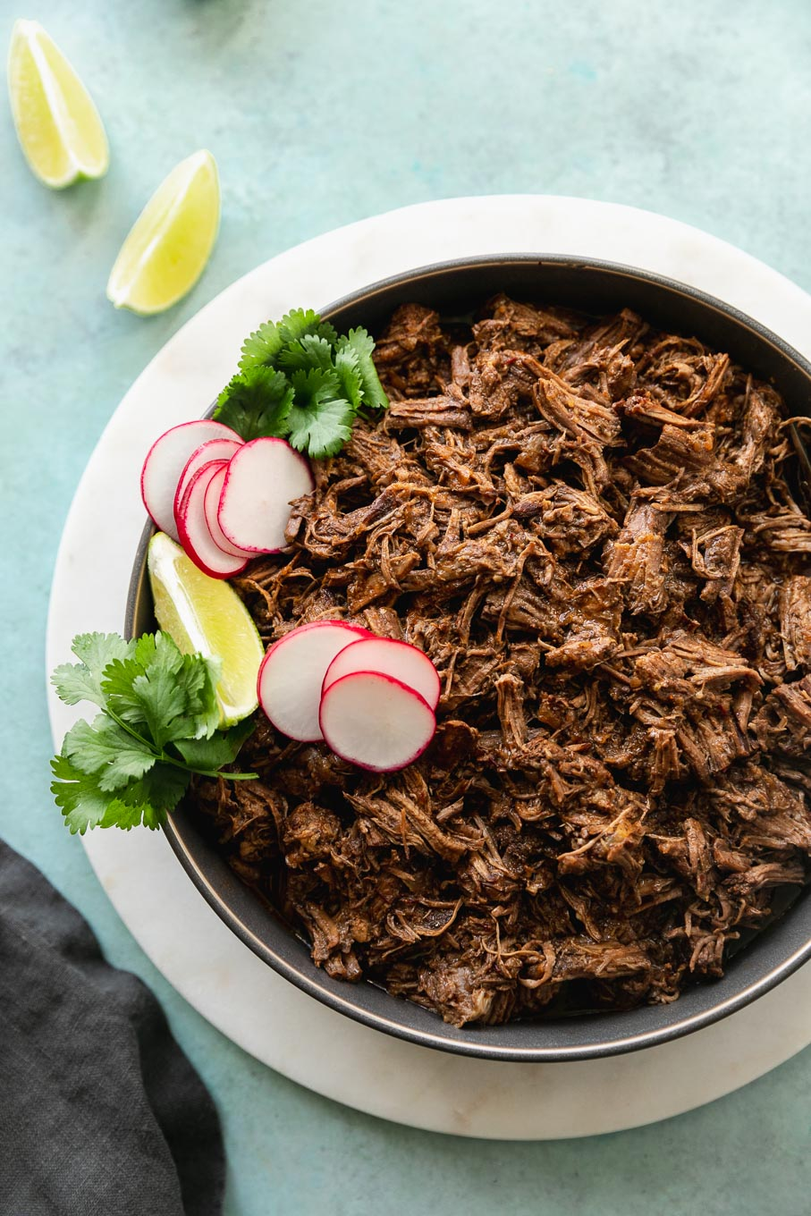 Overhead close up shot of a bowl of shredded barbacoa beef garnished with a lime wedge, cilantro, and sliced radishes