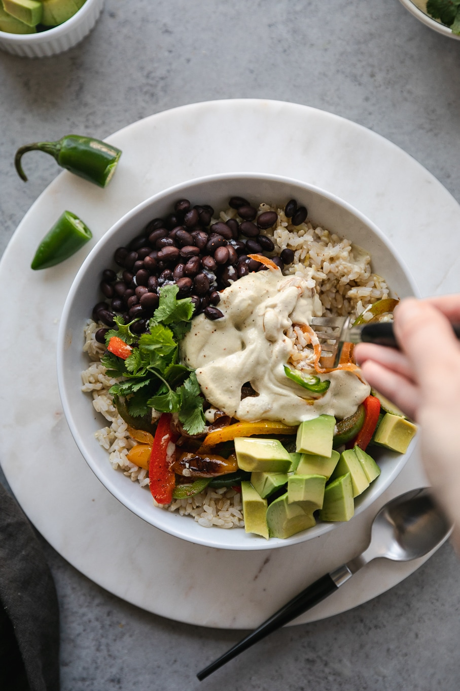 Overhead shot of a fajita burrito bowl topped with cashew queso and a fork taking a bite