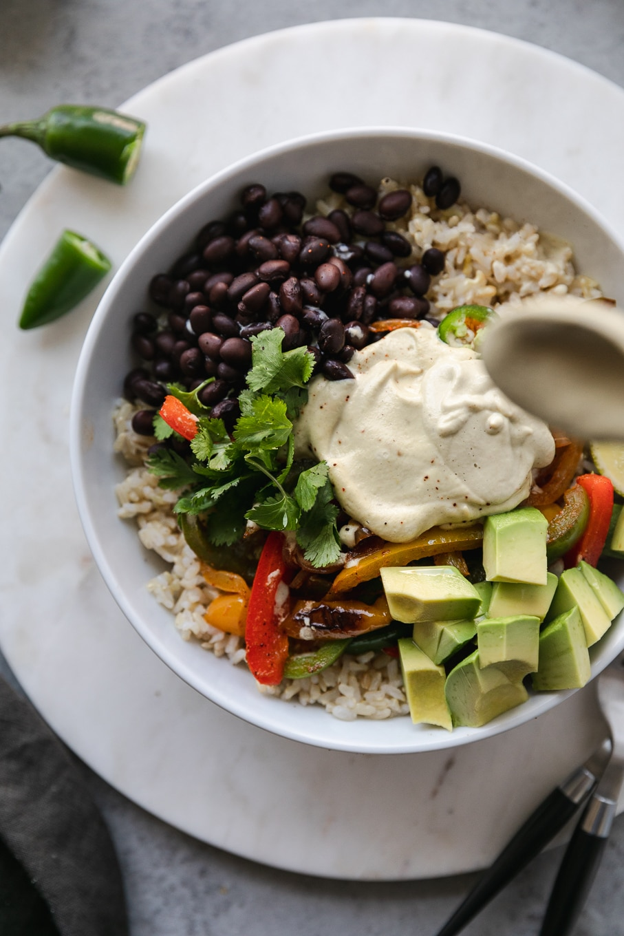 Overhead close up shot of a burrito bowl filled with black beans, fajita veggies, and avocado, being drizzled with cashew queso