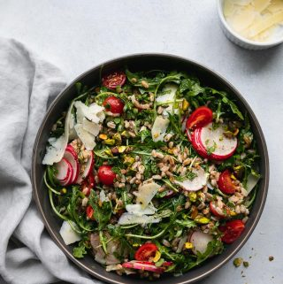 Overhead shot of a farro arugula salad topped with tomatoes, sliced radishes, shaved parmesan, and chopped pistachios