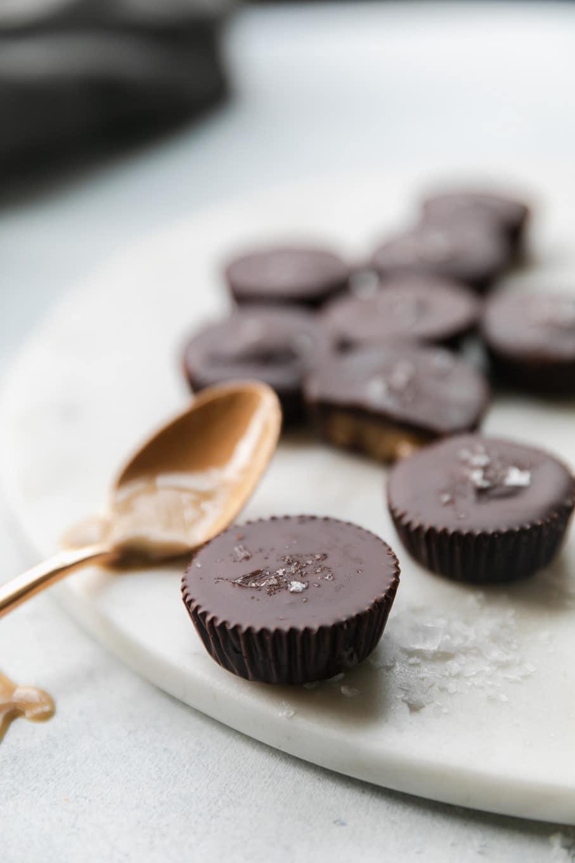 Close up shot of mini dark chocolate tahini cups with a spoonful of tahini next to it