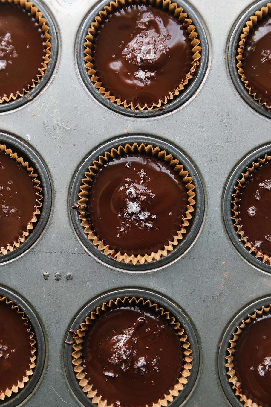 Overhead close up shot of a mini muffin tin filled with dark chocolate tahini cups and flaky sea salt on top of them