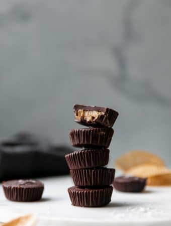 Forward facing shot of a stack of dark chocolate tahini cups with a bite taken out of the one on top