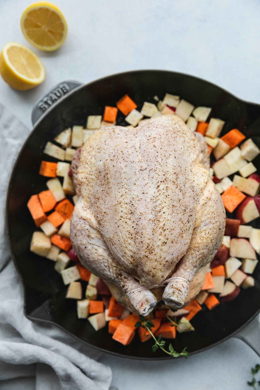 Overhead shot of a raw whole roasted chicken in a cast iron skillet on a bed of diced root vegetables