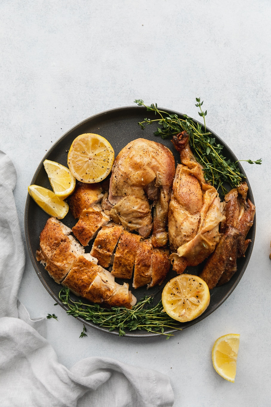 Overhead shot of a plate of roasted chicken garnished with thyme sprigs and lemon wedges