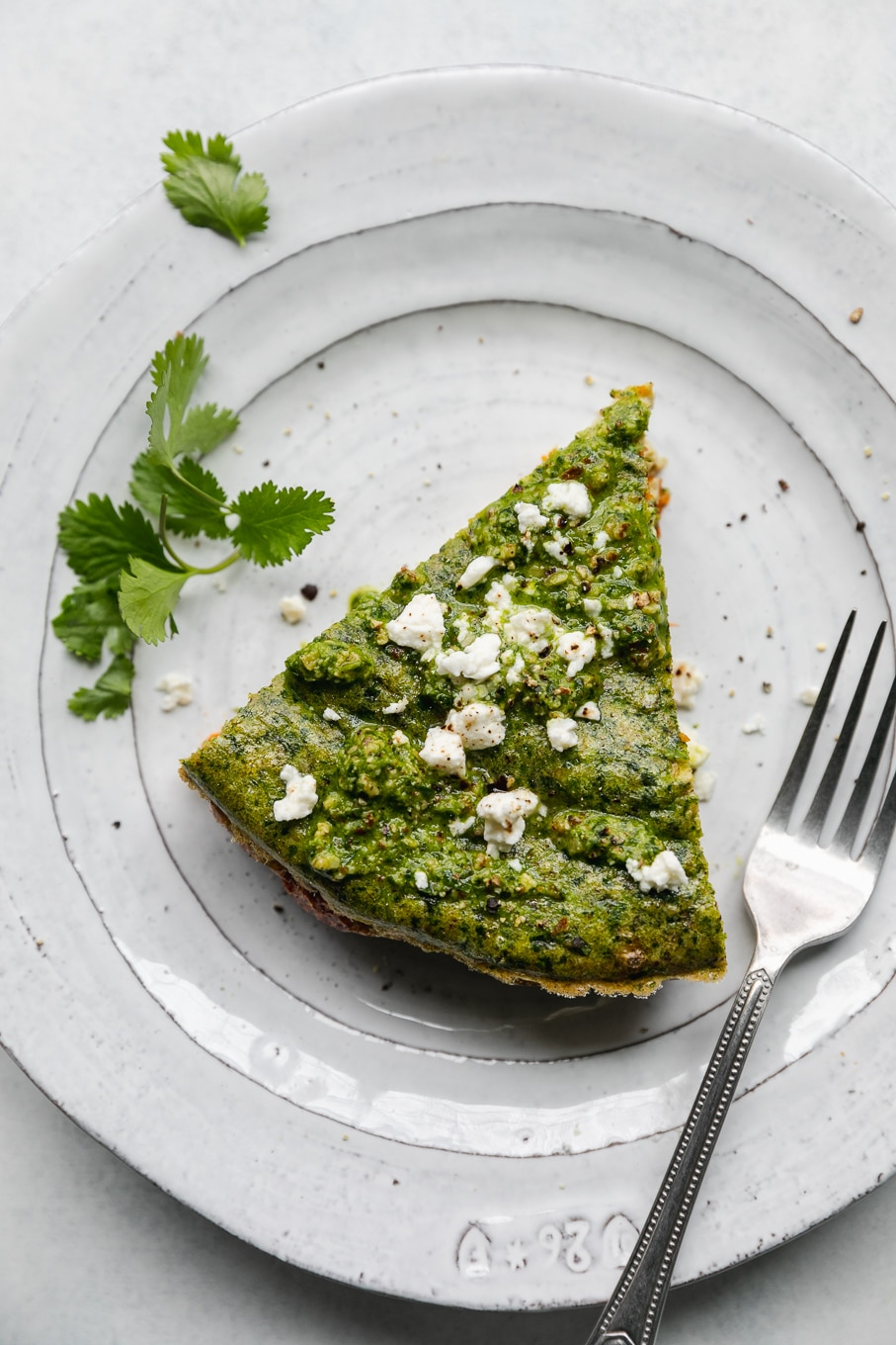 Overhead shot of a slice of cilantro pesto sweet potato frittata with crumbled feta on top on a white plate with a silver fork resting on the plate