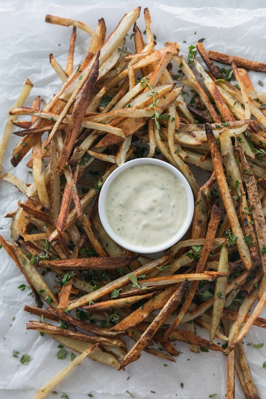 Overhead shot of a pile of thin french fries with herbs and a small bowl of aioli in the middle