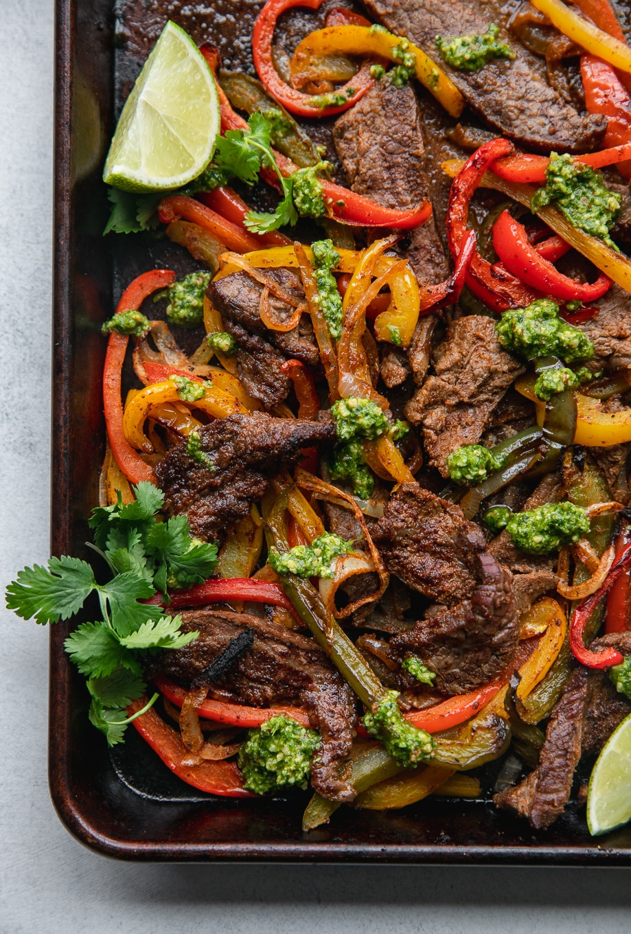 Overhead shot of a sheet pan filled with steak fajitas, peppers, and onions drizzled with cilantro pesto