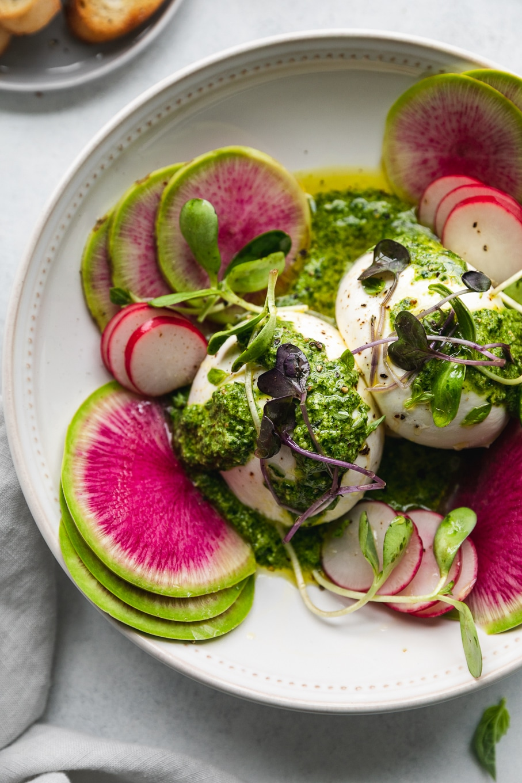 Overhead close up shot of green goddess pesto burrata with watermelon radishes and microgreens garnishing the bowl