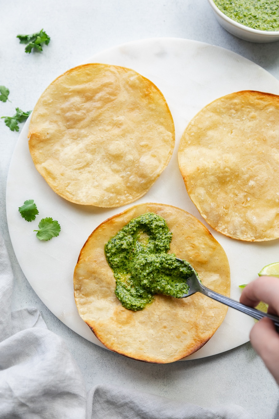 Overhead shot of 3 crisped tortillas on a marble board, the bottom tostada shell being spread with cilantro pepita sauce