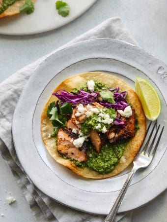 Overhead shot of a blackened salmon tostada with green sauce, red cabbage, queso fresco, cilantro, and a lime wedge on a white plate with a silver fork
