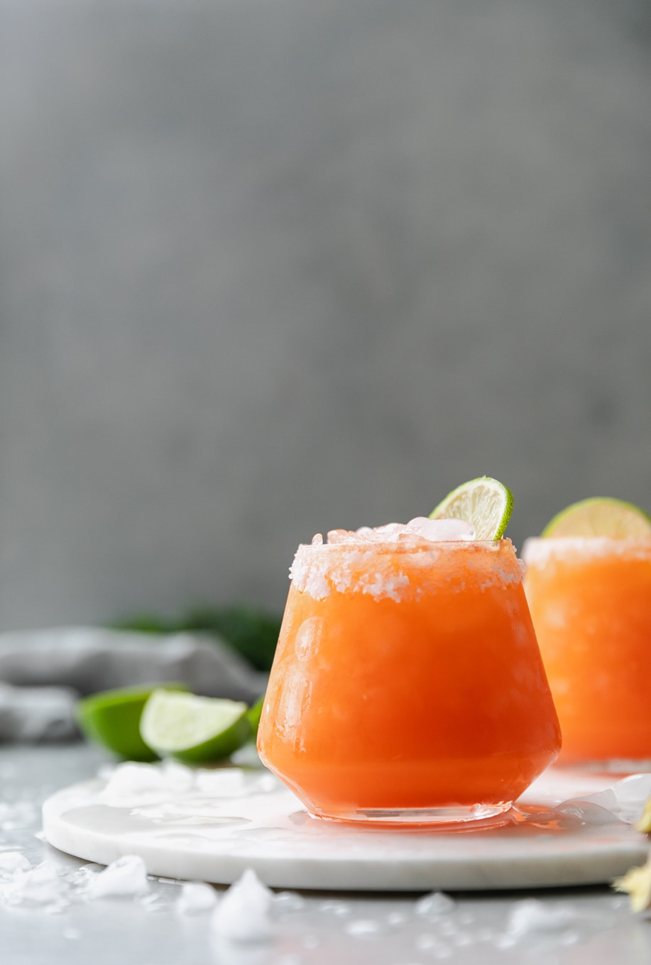 Forward facing shot of 2 carrot ginger margaritas on a circular marble board with lime wedges in the background and crushed, melted ice scattered around
