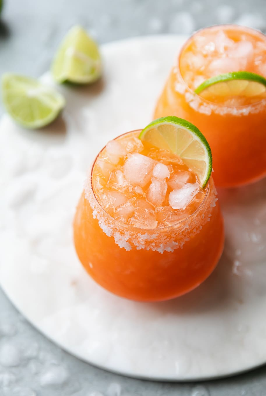Close up shot of 2 carrot ginger margaritas garnished with a lime slice