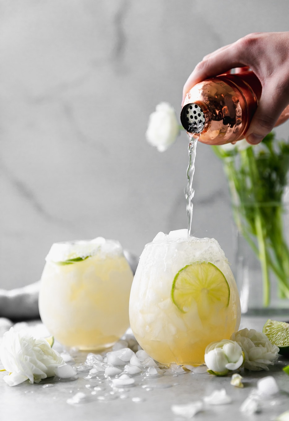Forward facing shot of two elderflower margaritas, with a bronze shaker pouring into the closest one with white flowers in the background