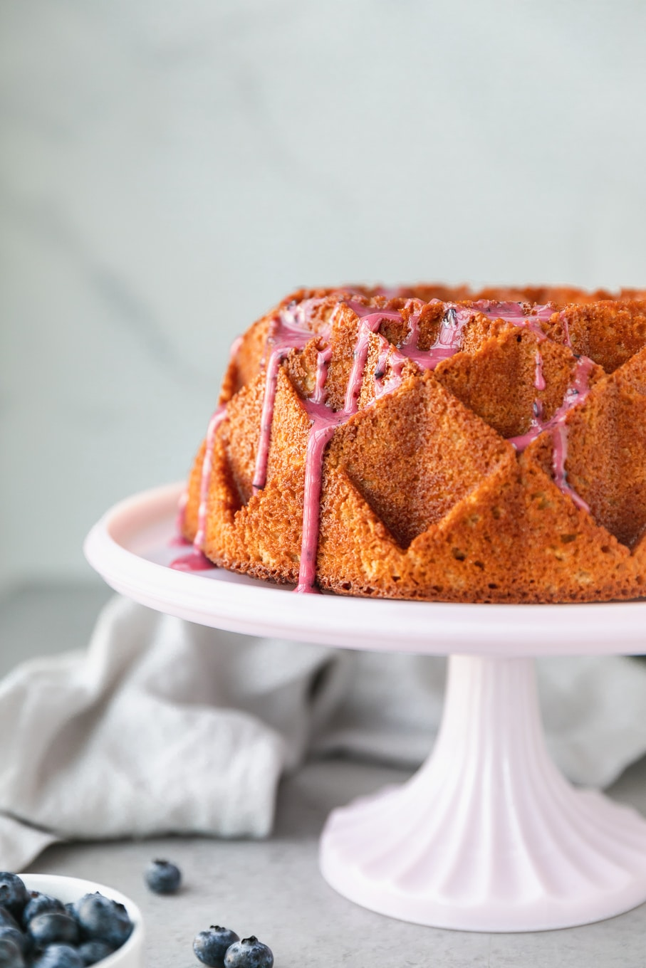 Close up shot of a lemon pound cake lightly drizzled with blueberry glaze on a light pink cake stand