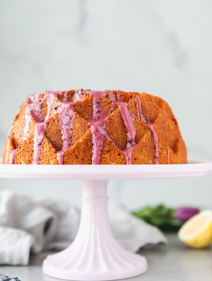 Forward facing shot of a lemon pound cake with blueberry glaze on a pink cake stand