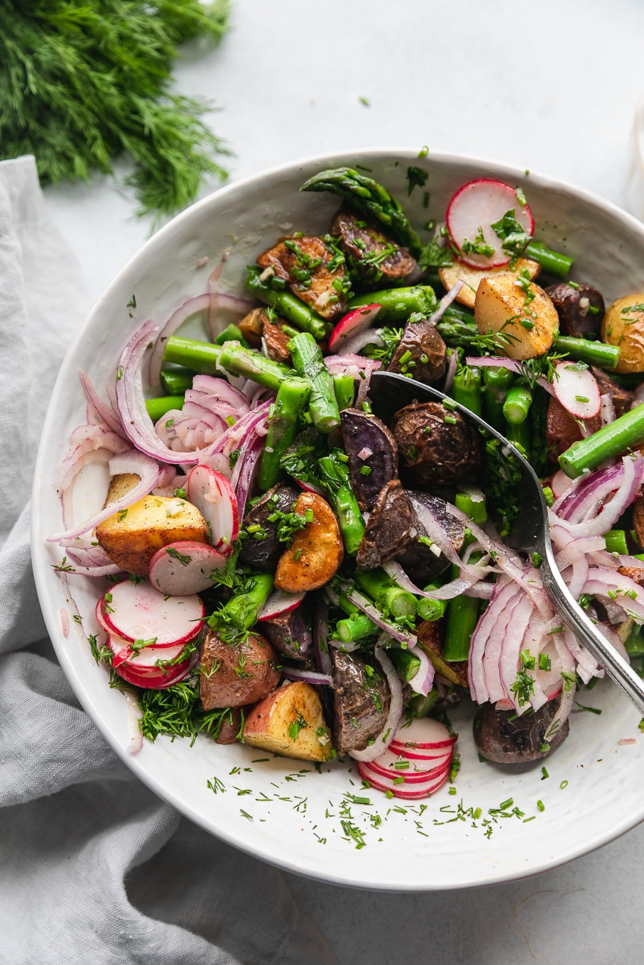 Overhead close up shot of a bowl filled with roasted potato salad with asparagus, sliced radishes, red onion, and fresh herbs being tossed with a silver spoon
