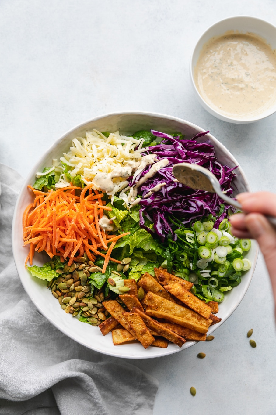 Overhead shot of a large mixing bowl filled with chopped romaine, shredded carrots, shredded white cheddar, shredded red cabbage, scallions, and tortilla strips being drizzled with a creamy sriracha ranch dressing
