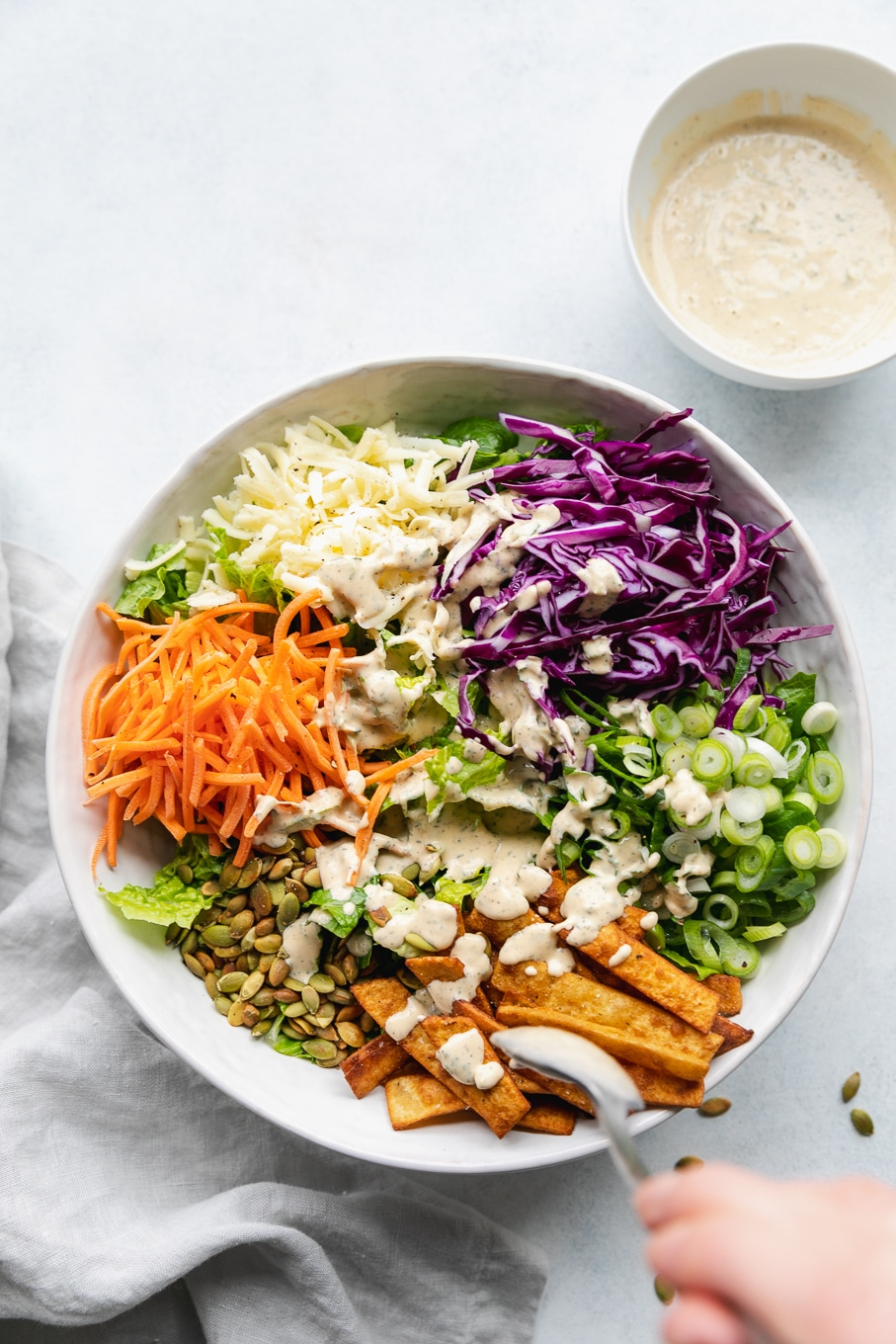 Overhead shot of a large mixing bowl filled with chopped romaine, shredded carrots, shredded white cheddar, shredded red cabbage, scallions, and tortilla strips topped with a creamy sriracha ranch dressing