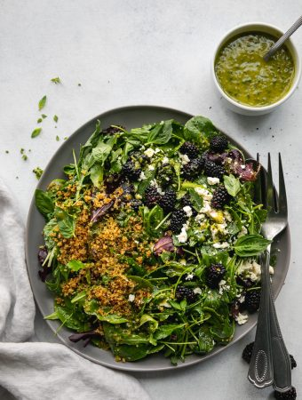 Overhead shot of a salad topped with crispy quinoa, blackberries, and feta