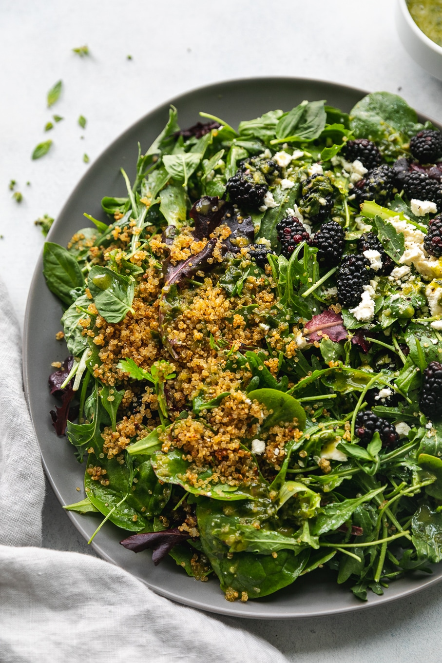 Overhead close up shot of a salad topped with blackberries, feta, and crispy quinoa