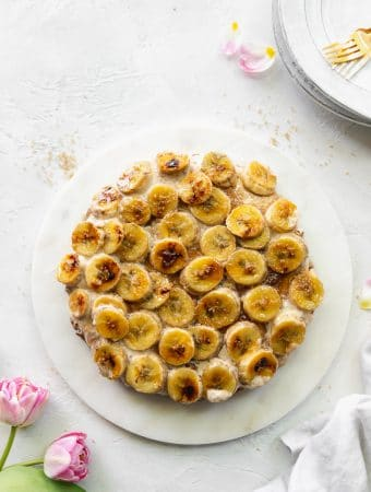 Overhead shot of a brûléed banana pie against a white background with pink tulips in the bottom left