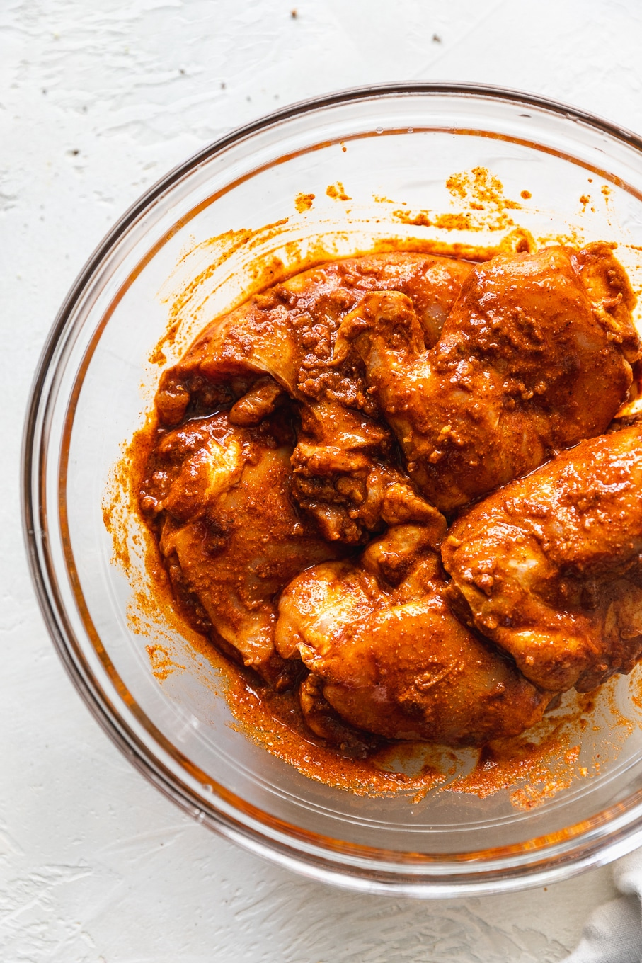 Overhead shot of a clear bowl filled with chicken marinating in bright orange and red spices