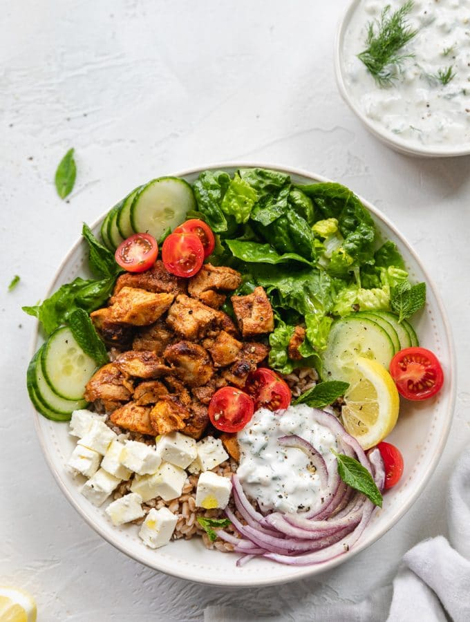 Overhead shot of a chicken shawarma bowl with cherry tomatoes, red onion, feta, cucumbers, romaine, mint, and tzatziki