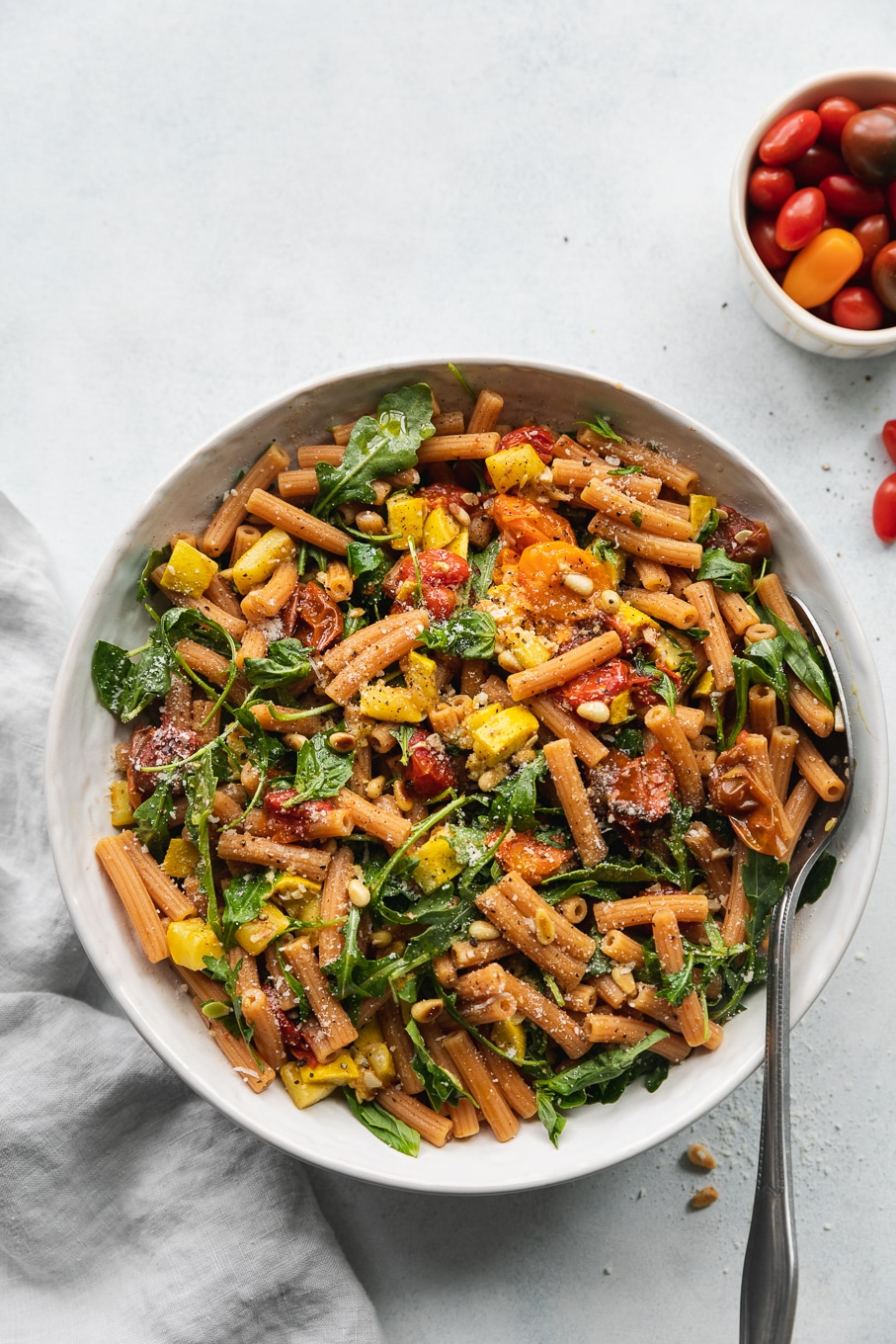 Overhead shot of a bowl of pasta filled with roasted tomatoes, summer squash, arugula, and parmesan cheese with a large silver utensil in the bowl