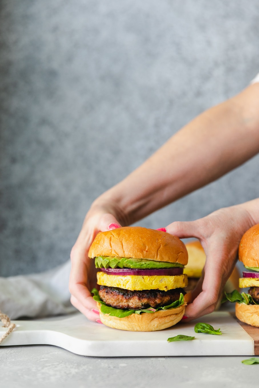 Forward facing shot of hands grabbing a burger