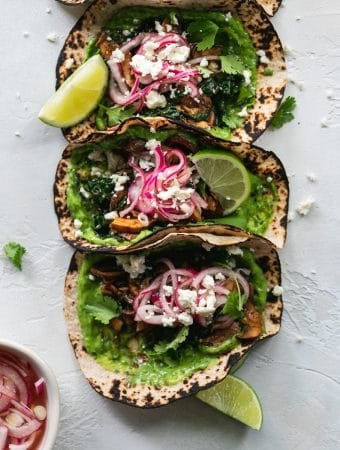 Overhead shot of 3 tacos with avocado cilantro sauce, pickled red onions, and lime wedges