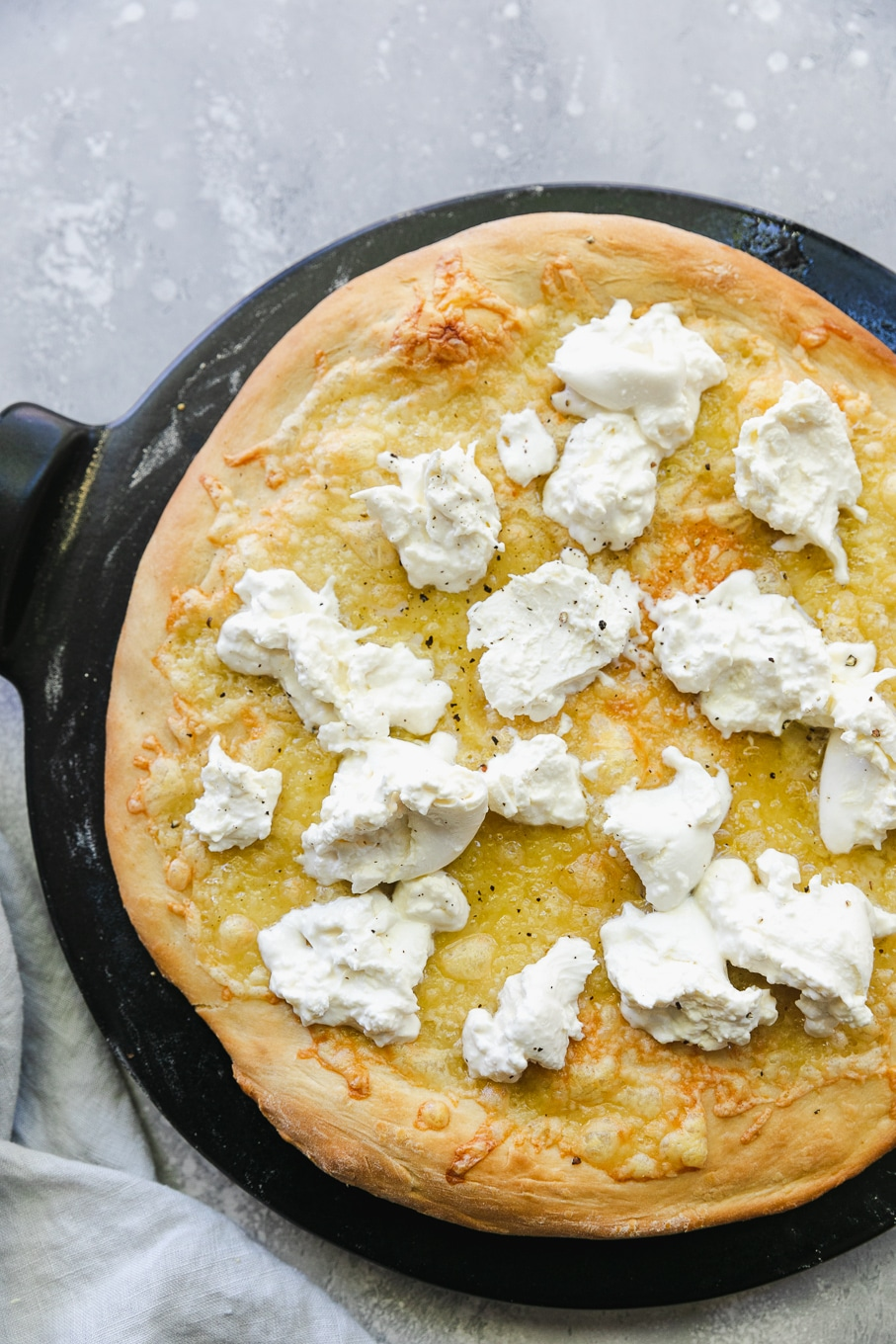 Overhead shot of a baked pizza crust topped with torn pieces of burrata cheese