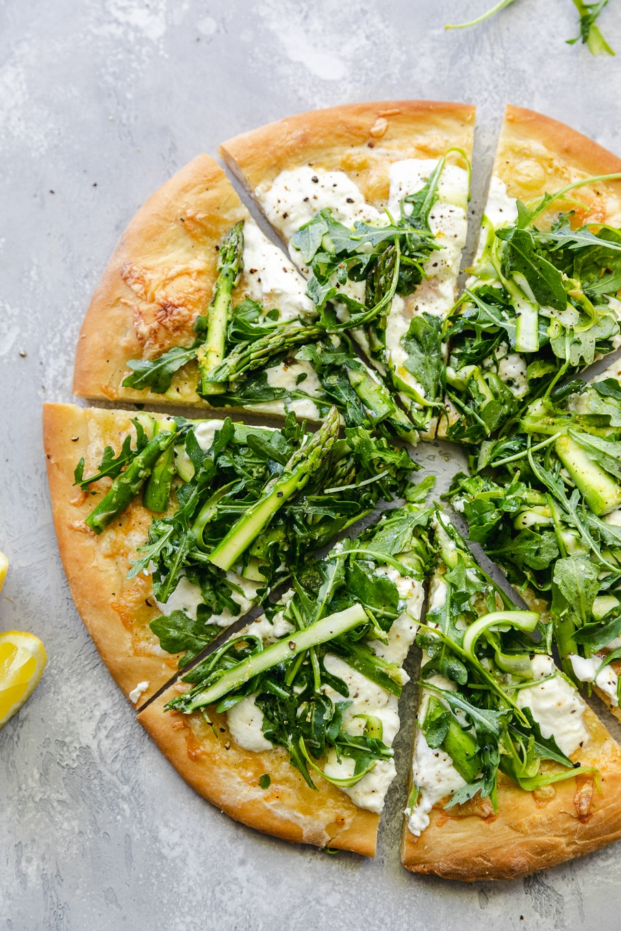 Overhead shot of a pizza cut into triangles topped with a shaved asparagus arugula salad