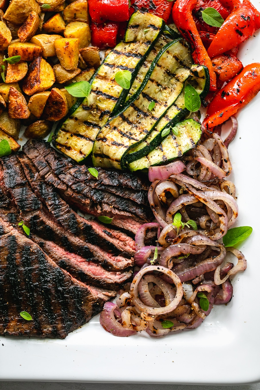 Overhead close up shot of a platter of flank steak, grilled vegetables, and roasted potatoes
