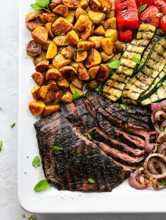 Overhead shot of a platter of flank steak, grilled vegetables, and roasted potatoes