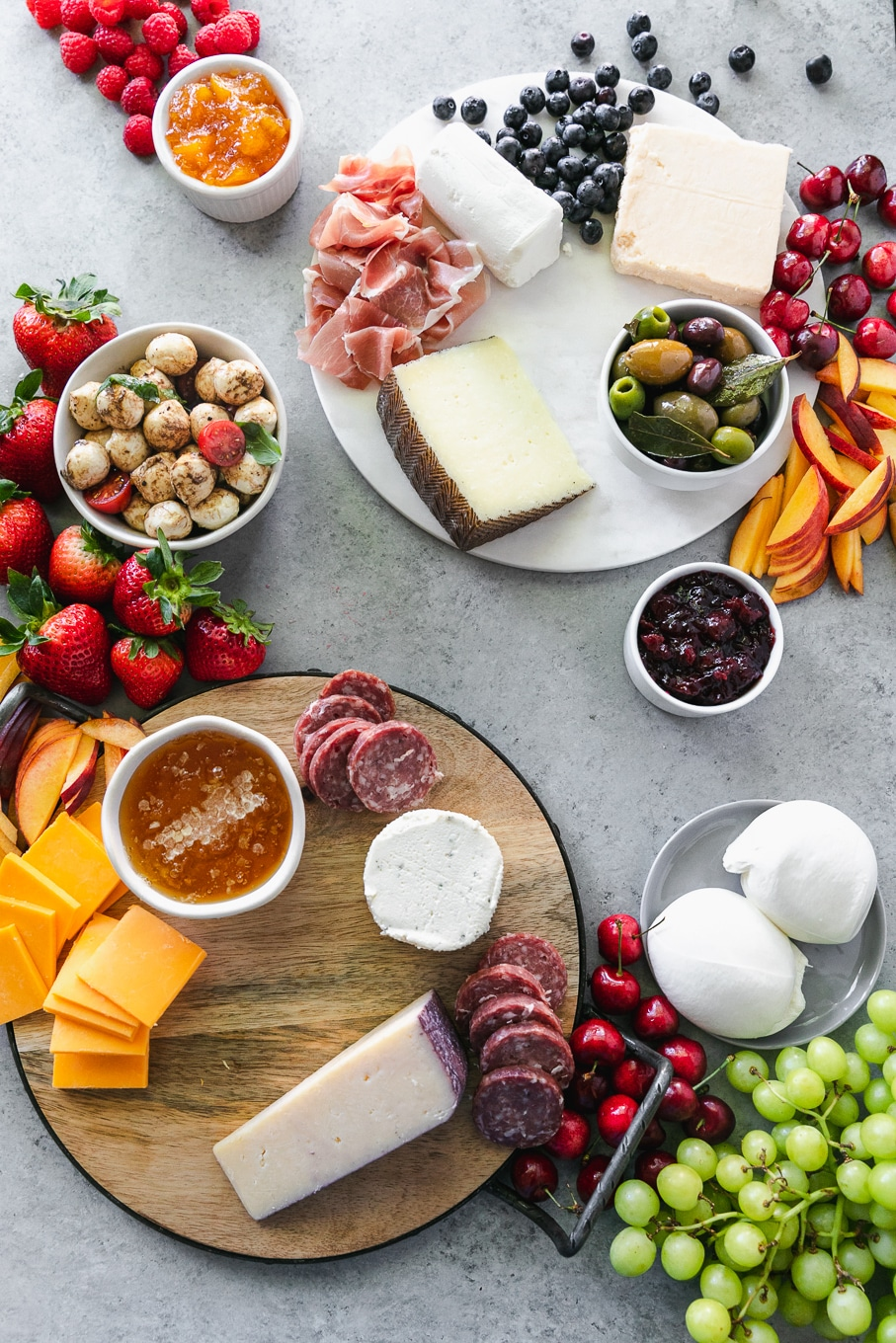 Overhead shot of cheeses, salami, and fruit