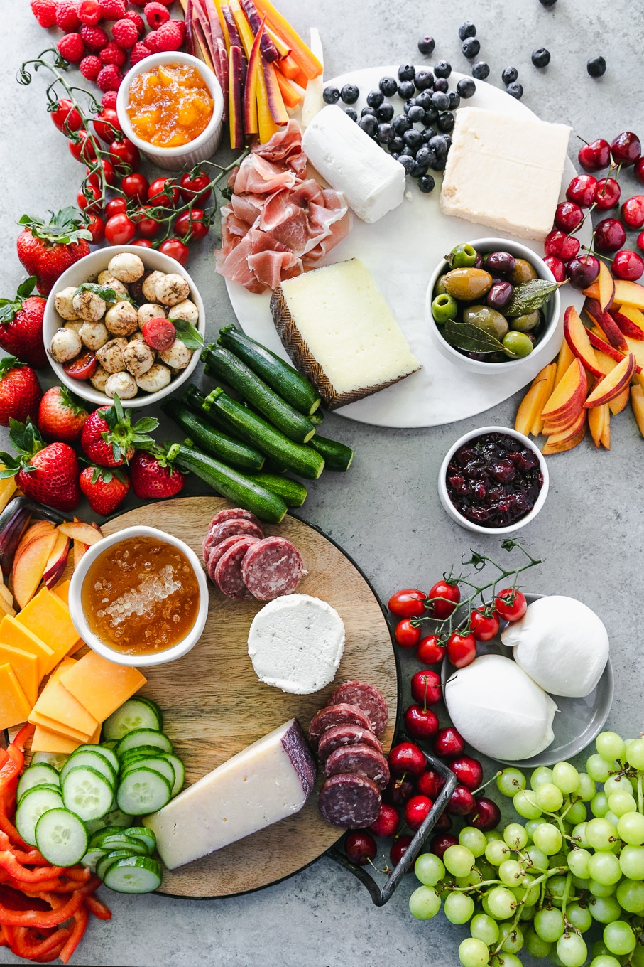 Overhead shot of cheeses, salami, fruit, and vegetables