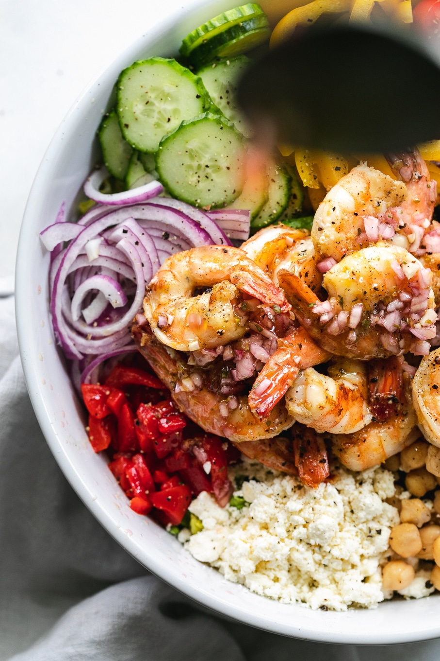 Overhead close up shot of a mediterranean chopped salad with shrimp being drizzled with vinaigrette