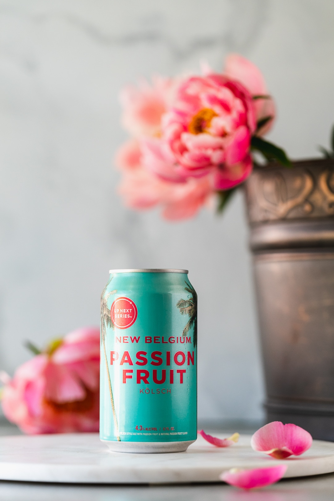 Colorful shot of a can of passionfruit beer with flowers in the background